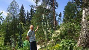 Mies osoittaa kädellään puutarhassaan olevaa kaktusta, joka on tehty betonista.