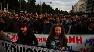 Ihmisiä kulkee kadulla mielenosoituslakanoiden kanssa, etualalla kaksi naista.