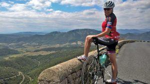 Nainen maantiepyörän selässä vuoristossa.