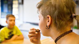 Tyttö laittaa suklaapalan suuhun.
