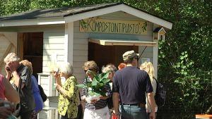 ihmisiä kompostointipuiston mökin luona
