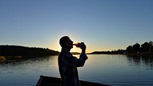 Mies juo alkoholia veneellä.
