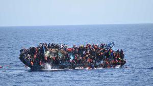 Ihmisiä täynnä oleva alus kallellaan meressä. Ihmisiä on jo pudonnut veteen.