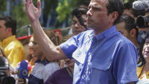 Caprilers seisoo väkijoukossa vakavan näköisenä, oikea käsi ojennettuna ylevään eleeseen. Hänellä on yllään sininen lyhythihainen kauluspaita. Taustalla on muita mielenosoitukseen osallistuvia ja televisiokameroita.