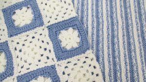 Sinivalkoisia käsinkudottuja peittoja.