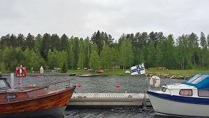 Venesatama jossa kaksi venettä, taustalla veneilijöiden tukikohta