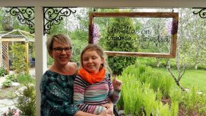 Tiina ja Reetta Piippo, taustalla pihaa ja kukkapenkkejä.