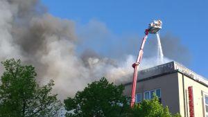 Palokunnan nostokurjesta ruiskutetaan vettä savuavaan rakennukseen.