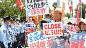 Rivi sotilaita kasvosuojuksissaan tarkkailee iäkkäitä mielenosoittajia, joiden kylteissä vaaditaan englanniksi ja japaniksi, että kaikki tukikohdat suljetaan.