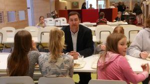 Mies istuu koulun ruokalassa oppilaiden keskellä ja katsoo kameraan.