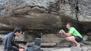 Kaksi nuorta miestä kallionkielekkeen alla, toinen istuu kannettavan tietokoneen ääressä, toinen kyyköttää pidellen skanneria kohti kielekkeen kattoa.