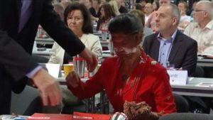 Punapukuinen nainen naama tahriintuneena kakusta.