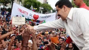 Venezuelan presidenttiä tukeva mielenosoitus. Vaaleaan kauluspaitaan pukeutunut Maduro ojentaa hymyillen korokkeelta kättään väkijoukkoon.