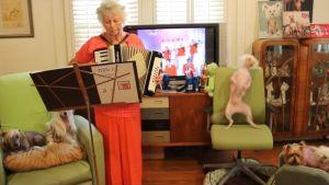 Tillie-mummo soitaa haitaria ja Nathan-koira tanssii.
