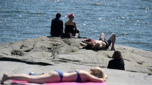 Auringosta nauttijoita Helsingin Kaivopuistossa tiistaina.
