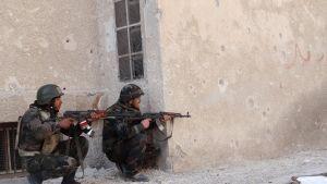 Kaksi Syyrian hallituksen sotilasta kyykistyy seinän viressä rynnäkkökiväärit kädessään.