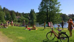 Mikkelin Pitkäjärveln uimarannalla auringonpalvojia nurmikolla.