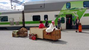 nainen ja lapsi ottavat vastaan junamatkustajia puulaatikoiden päällä