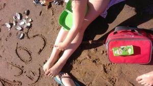 Lapset syövät eväitä Ajoksen hiekkarannalla