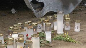 Nuorukaisen muistolle tuotuja kynttilöitä.