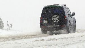 Auto lumisella tiellä Inarissa kesäkuussa.