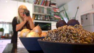 Bloggaaja Johanna Koskiranta kuvaa asetelmaa keittiössään Hellan ja viinilasin välissä-blogiaan varten