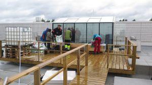 Työntekijöitä häärii Tampere-talon katolla olevan kasvihuoneen vieressä.