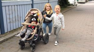 Milla Maria Lassila työntää lastenvaunuja tyttärensä kanssa.