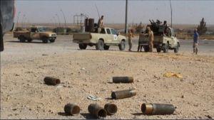 Hylsyjä maassa. Kauempana taistelijoita ja avolava-autoja, joissa on konekiväärejä pultattuna lavalle.