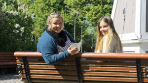 Kaksi nuorta naista puistonpenkillä.