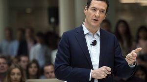 Osborne puhuu viittilöiden käsillään. Hänellä on tummansininen puku ja kauluspaita ilman kravattia. Mikrofoni on kiinnitetty hänen paitaansa. Taustalla näkyy yleisöä.