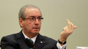 Eduardo Cunha istuu mikrofonin takana ja pitää vasenta kättään pystyssä.