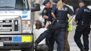 Kyykyssä istuva aktivisti kolmen poliisin ympäröimänä.