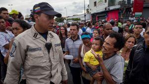 Mies pitää lasta sylissään ja puhuu poliisille ihmisjoukon keskellä.