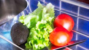 Avokado, salaaattia ja tomaatteja tiskipöydällä.