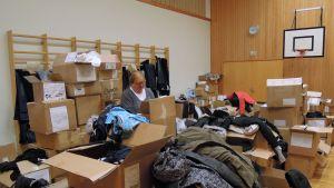 Tuija Vuorenranta lajittelee vaatteita Oinasjoen koululle perustetussa ompelutyöpajassa.