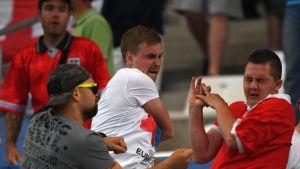 Kolme miestä kädet nostettuina; oikeanpuolimmainen näyttää saaneen juuri iskun keskimmäiseltä.
