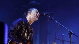 Radioheadin laulaja Thom Yorke lavalla kitaran ja mikrofonin kanssa.