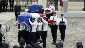 Poliisit kantavat Ranskan lipuilla verhottuja arkkuja.