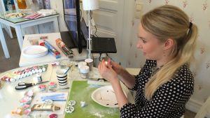 Nainen tekee kakun koristeita.
