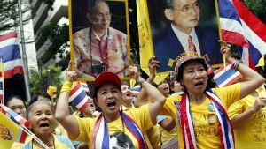 """Joukko Thaimaan lippuja ja kuninkaan kuvia kantavia ihmisiä huutaa """"Eläköön kuningas!"""" sairaalan ulkopuolella Bangkokissa viime joulukuussa."""