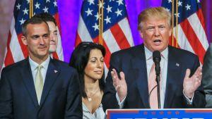 Kuvaa kampanjatilaisuudesta. Corey Lewandowski seisoo kuvan vasemmassa reunassa tummassa puvussa vieno hymy kasvoillaan, Trump puhuu kuvan oikeassa reuanssa käsillään puhetta painottaen.