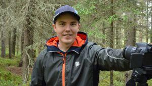 Nuori mies metsässä kameran kanssa.