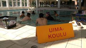Maahanmuuttajia uimakoulussa. Uimakoulukyltti uima-altaan reunalla.