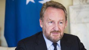 Bakir Izetbegović, taustalla EU:n lippu.