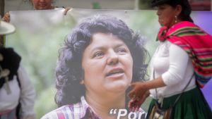 Nainen pitelee suurta Berta Cáceresin kuvaa. Toinen nainen on kävelemässä julisteen ohi.