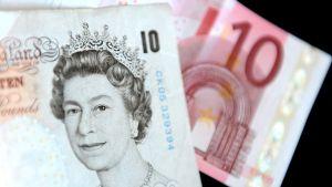 Kuva 10 punnan ja 10 euron seteleistä. 10 punnan setelissä on kuningatar Elisabet toisen kuva. Euron seteli on lohenpunainen.