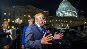 Protestia johtava demokraattien kongressiedustaja John Lewis puhuu kongressirakennuksen edustalla.