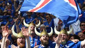 Islantilannin lipun väreihin pukeutuneita jalkapallofaneja. Etuan miesjoukolla on viikinkihatut ja he heiluttavat Islannin lippua.