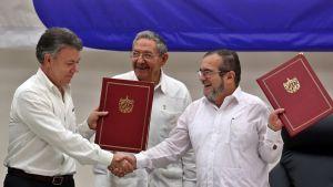 Londono ja Santos kättelevät. Toisessa kädessä kummallakin on koristeellinen kansio. Taustalla Raúl Castro.